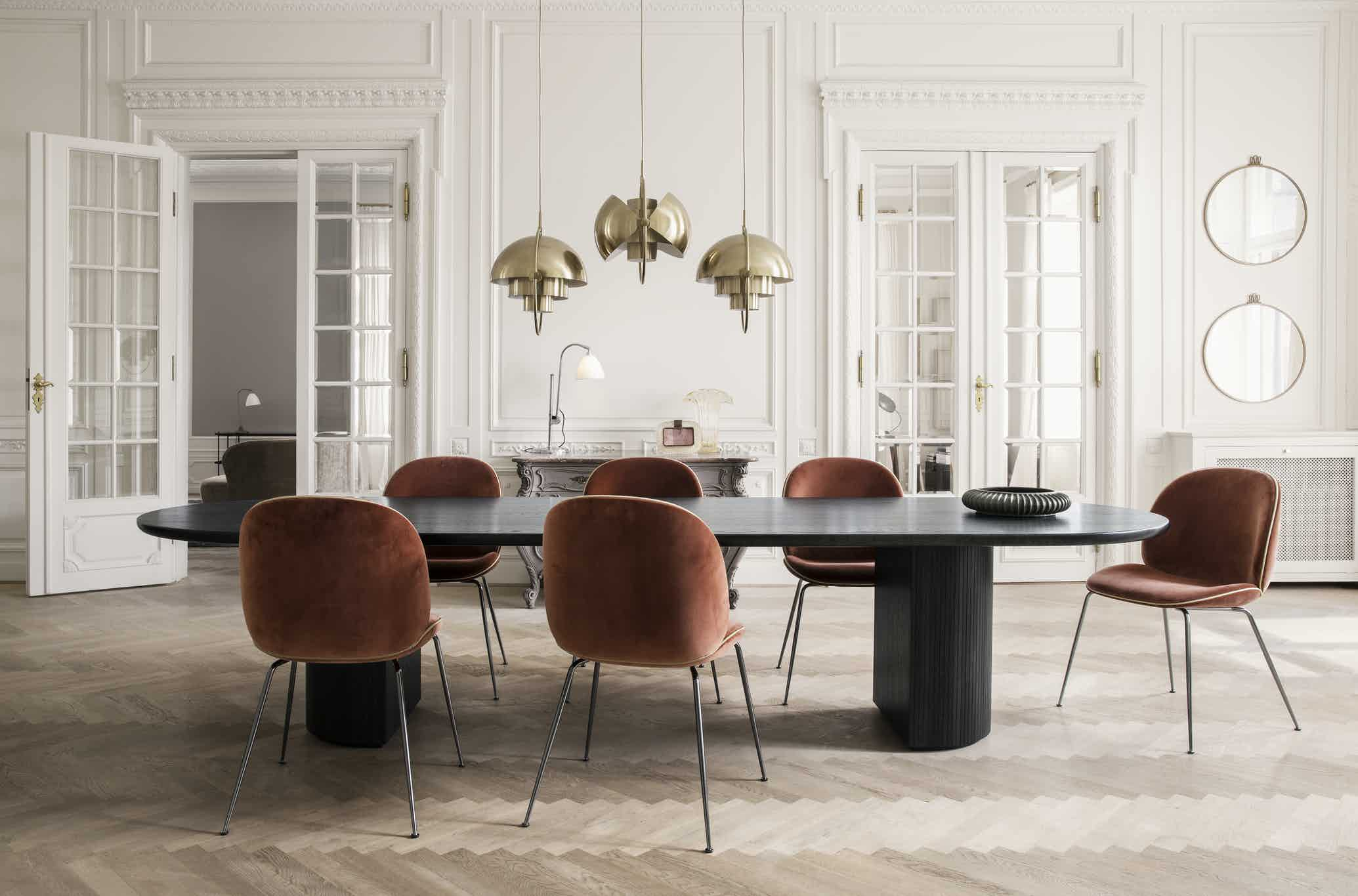 Designed by Space Copenhagen, the classic Moon Dining Table features an interplay between a beautiful solid oak table top and a smooth half or full moon shaped base with bevelled surface.