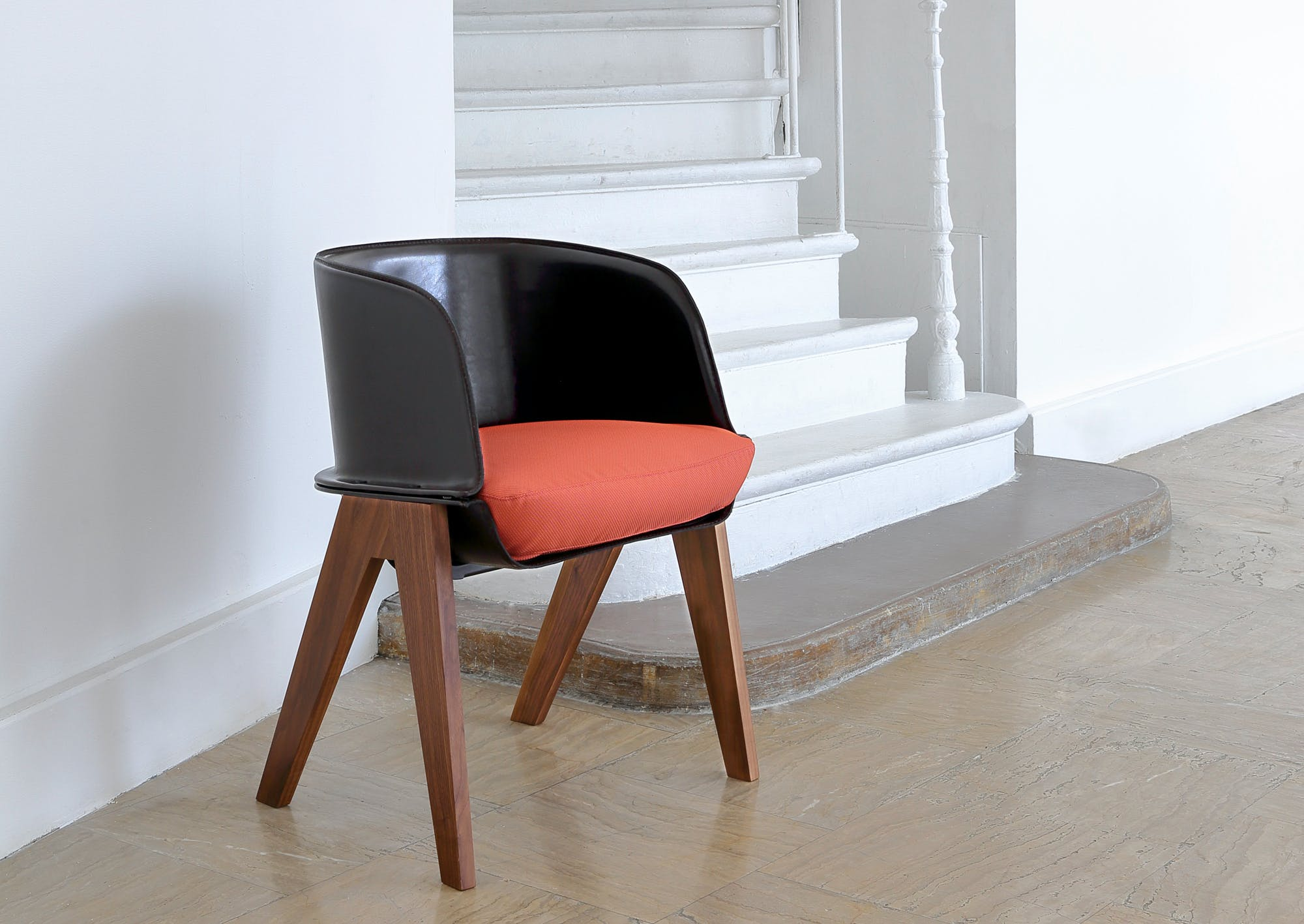 LUCIA by PATRICIA URQUIOLA | COEDITION The Lucia Chair, designed in 2014 by the venerable Patricia Urquiola, boasts a unique form with a black or brown leather shell, an upholstered seat, and walnut or black ash legs.